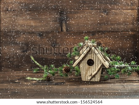 christmas tree decoration and birdhouse over rustic wooden background. vintage country style picture with snowflakes - stock photo