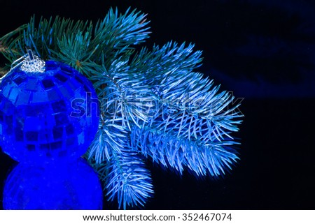 Christmas tree decoration blue ball on a black glass background and a branch of Christmas tree  - stock photo