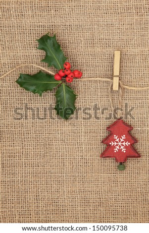 Christmas tree decoration with holly berry sprig hanging on a line over hessian background. - stock photo