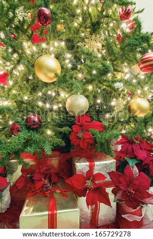 Christmas Tree Decoration with Lights Ornaments Ribbons Poinsettia and Presents Under the Tree - stock photo