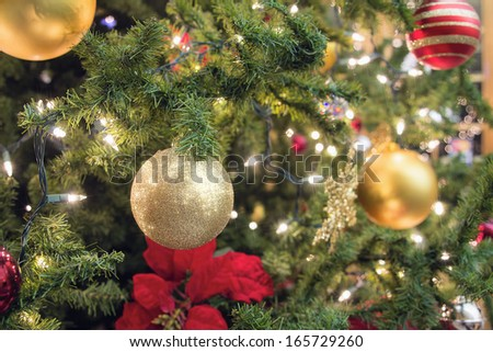 Christmas Tree Decoration with Ornaments Lights and Poinsettia Closeup - stock photo