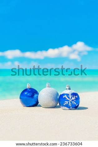 Christmas tree decorations on sea beach sand - winter holidays in hot countries concept - stock photo