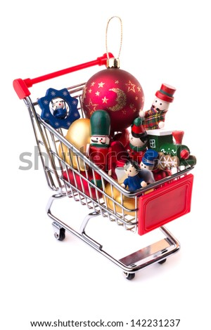 Christmas-tree decorations: shopping cart, full of Christmas toys and baubles, isolated on white background