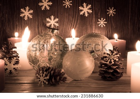 Christmas tree decorations with candles on an old wooden background - stock photo