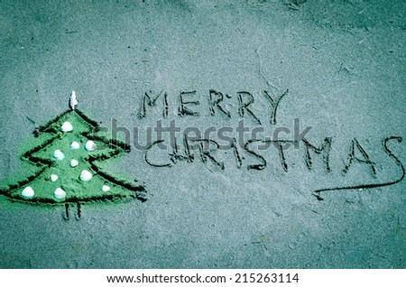 Christmas tree drawn into sand on beach - stock photo