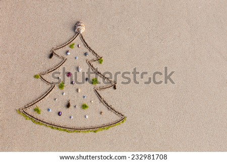 Christmas tree drawn on the sand and decorated with seashell and algae - stock photo
