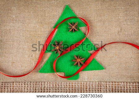 Christmas tree from felt with star anise and red ribbon on brown sackcloth - stock photo