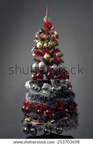 Christmas tree, full lenght,against grey background, silver,gold red ornaments... - stock photo