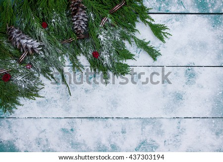 Christmas tree garland border and pine cones border antique teal blue snowy wood background - stock photo