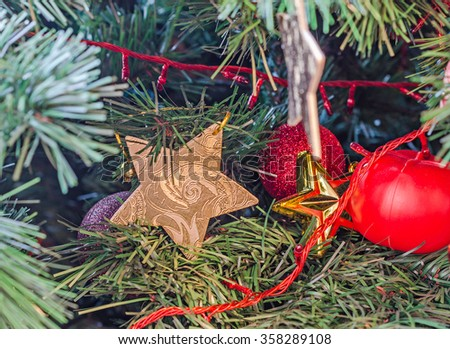 Christmas tree golden star ornament, globe hanging, snow flake, green tree, firs, close up. - stock photo