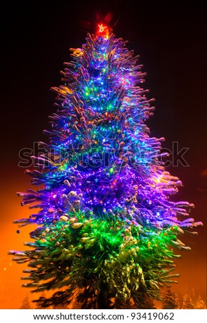 Christmas tree in the town sparkling over dark sky. - stock photo