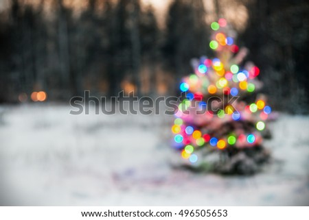 Christmas tree in winter forest with colored lights blurred background. vignette for artistic effect