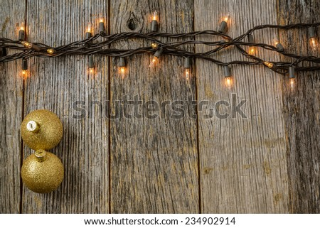 Christmas Tree Lights with Rustic Wood Background and Gold Ornaments - stock photo