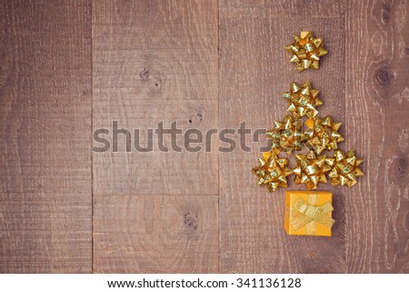 Christmas tree made from decorative bows and gift boxes on wooden background. View from above - stock photo