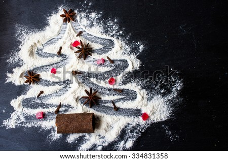 Christmas tree made from flour on a black background with anise stars and cinnamon sticks - stock photo