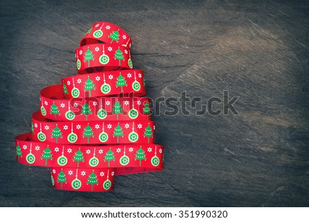 Christmas tree made from ribbon with copy space on wooden background ; vintage tone - stock photo