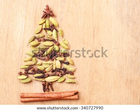 Christmas tree made from spices cinnamon stick anise star cardamon pods and cloves on wooden background - stock photo