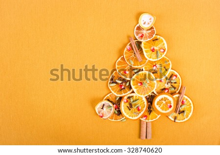 Christmas tree made of dried oranges, cinnamon and anise. Viewed from above. - stock photo