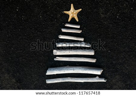 Christmas tree made of driftwood and starfish on black lava sand. Space for cropping and text. - stock photo