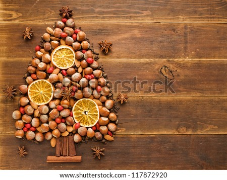 Christmas tree made of nuts, spices and dried oranges. Viewed from above. - stock photo