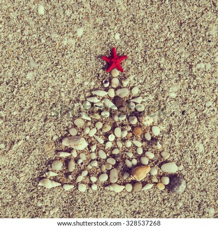 Christmas tree made of pebbles and seashells with a red starfish on top of it - stock photo