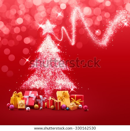 Christmas tree made of sparkles and lights with gifts and baubles on red background - stock photo