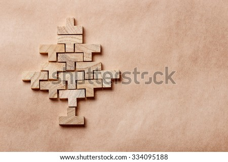Christmas tree made of wooden bricks on brown backdrops - stock photo