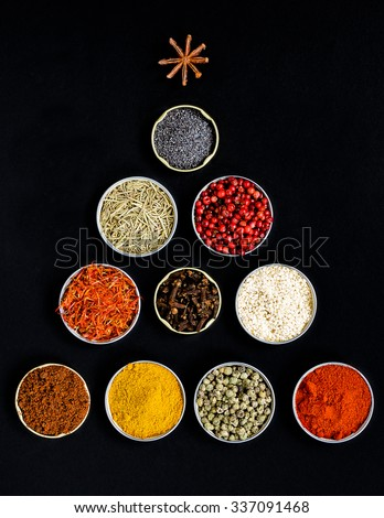 Christmas tree of assorted colorful spices on black background  - stock photo