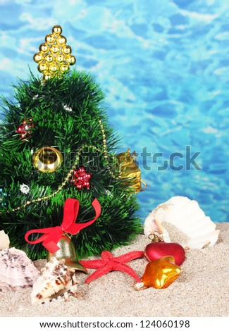 Christmas tree on sand in beach - stock photo