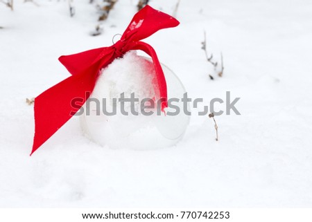 Christmas tree ornaments positioned in a snow setting with white background