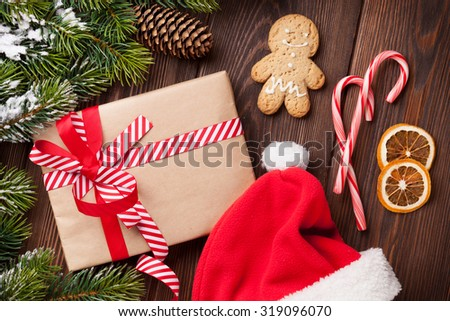 Christmas tree over wooden background with santa hat, gingerbread man and gift box - stock photo