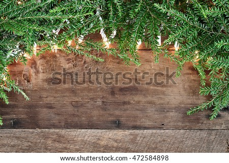 Christmas tree pine branches and decorative lights over a rustic background of barn wood. Image shot from overhead.