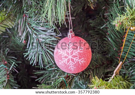 Christmas tree red ornament, globe hanging, snow flake, green tree, firs, close up. - stock photo