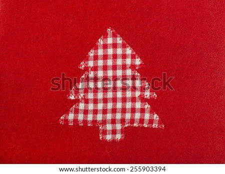Christmas tree shape on red wool background. Checkered tablecloth fabric tree sewed on red. - stock photo