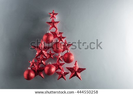 Christmas tree shape with red stars and baubles over color background - stock photo
