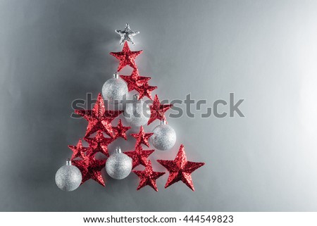 Christmas tree shape with red stars and silver baubles over color background