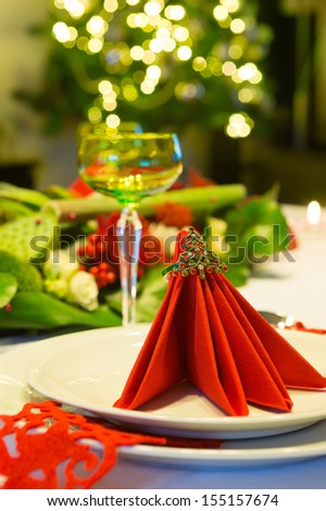 Christmas tree shining behind a decorated christmas dinner table with red napkins - stock photo