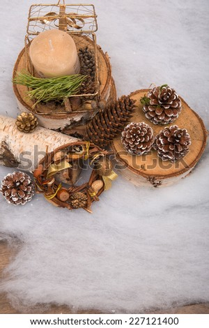 Christmas tree toys  and decoration like  fir branch and box with candle wooden log and pine and fir cones  and wreath of nuts hazel  peanuts  on snow with   top view - stock photo