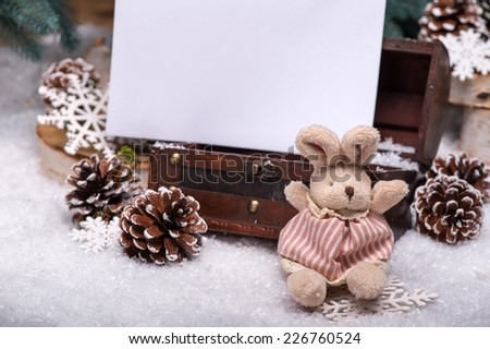 Christmas tree toys  like   cones  and plush rabbit  and wooden  box  and snowflakes  and sheet of paper on snow near  fir with selective focus copy place  - stock photo