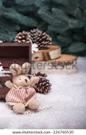 Christmas tree toys  like   cones  and plush rabbit  and wooden  box  and snowflakes on snow near  fir with selective focus  - stock photo