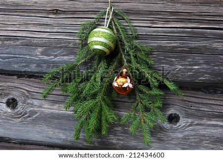 Christmas tree twig and decorations against the background of the shabby wooden wall - stock photo