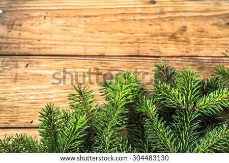 Christmas tree twigs of spruce arranged on aged wooden planks background useful as holiday background in vintage style. - stock photo