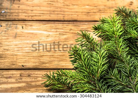 Christmas tree twigs of spruce arranged on old wooden planks background useful as holiday background in vintage style. - stock photo