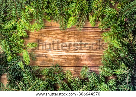 Christmas tree twigs of spruce on a wooden planks background useful as holiday background in vintage style. Arrangement in frame pattern. - stock photo