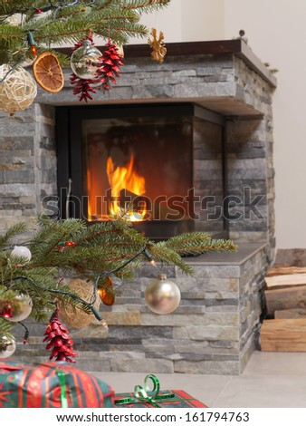 Christmas tree with christmas presents by the lit fireplace