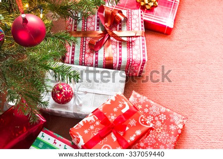 Christmas tree with gifts on red carpet - stock photo