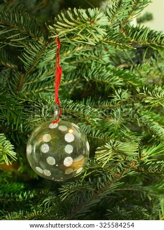 Christmas tree with glass bauble on red string, traditional decoration closeup background copy space.  - stock photo