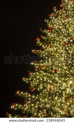 Christmas tree with golden lights and red bows at Frankfurt-at-Main, Germany - New Year and Christmas background and postcard