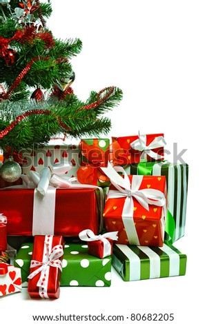 Christmas tree with heap of red gift boxes decorated with satin ribbon isolated on white background - stock photo