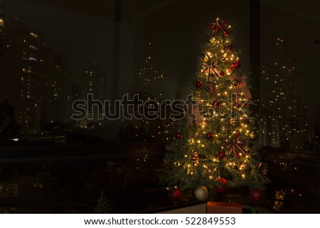 Christmas tree with lights on, in front of a city landscape at night